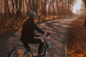 Frau sitzt auf einem Fahrrad. Im Hintergrund sieht man eine Herbstlandschaft.
